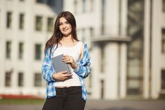 Student woman with books in hands standing on university buildin stock photo