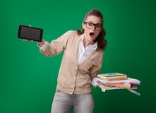 Student woman with books, notes and records and tablet PC. Shocked young student woman with books, notes and records and tablet PC showing the convenience of royalty free stock image