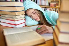 Student or woman with books sleeping in library. People, education, session, exams and school concept - tired student girl or young woman with books sleeping in Royalty Free Stock Photos