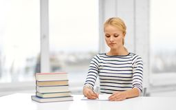 Student woman with books writing to notebook. Education, school and learning concept - student woman with books writing to notebook royalty free stock photography