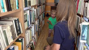 Student woman choosing book for her little daughter girl in library. stock video footage