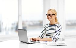Student woman in glasses with laptop and book. Education, school and learning concept - student woman in glasses with laptop computer and book at home stock images