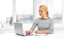 Student woman with laptop and notebook. Education, school and learning concept - student woman with laptop computer and notebook at home royalty free stock images