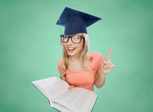 Student woman in mortarboard with encyclopedia. People, education, knowledge and graduation concept - smiling young student woman in mortarboard and eyeglasses Stock Photo