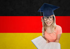 Student woman in mortarboard with encyclopedia. People, national education, knowledge and graduation concept - smiling young student woman in mortarboard and Royalty Free Stock Photos