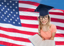 Student woman in mortarboard with encyclopedia. People, national education, knowledge and graduation concept - smiling young student woman in mortarboard and Royalty Free Stock Photo