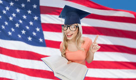 Student woman in mortarboard with encyclopedia. People, national education, knowledge and graduation concept - smiling young student woman in mortarboard and Royalty Free Stock Image