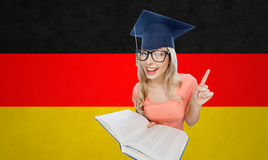 Student woman in mortarboard with encyclopedia. People, national education, knowledge and graduation concept - smiling young student woman in mortarboard and Stock Images