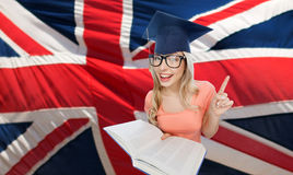 Student woman in mortarboard over english flag. People, national education, knowledge and graduation concept - smiling young student woman in mortarboard and Stock Photos