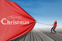 Student woman pulling big christmas banner Stock Photography