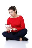 Student woman sitting cross-legged using a tablet Stock Photo