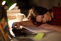 Student or woman sleeping on table at night home Stock Photos