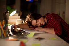 Student or woman sleeping on table at night home. Education, freelance, overwork and people concept - tired student woman sleeping on table at night home Stock Photos