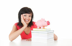 Student woman with stack of books and piggy bank Royalty Free Stock Image