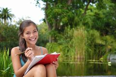 Student woman studying on campus park. Female student outdoors in the campus park studying and taking notes. Beautiful smiling mixed race caucasian / chinese Royalty Free Stock Image