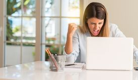 Young beautiful student woman with laptop at table, at home stock images