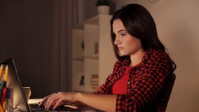 Student or woman typing on laptop at night home. Education, business, overwork and people concept - tired woman or student girl typing on laptop computer at stock footage