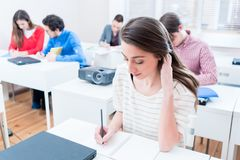 Student woman writing test in seminar room of university. Student women writing test in seminar room of university or having exam Stock Photography