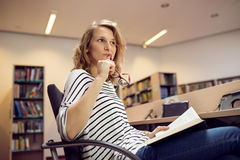 Student wondering or thinking about something. holding glasses i. Holding glasses in hand. Portrait of clever student with open book reading it in college Royalty Free Stock Image