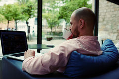 Student work on netbook drinking tea or black coffee while he sitting in modern hotel interior Stock Photos