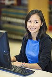 Student working at computer. Beautiful asian student working at computer in the library Stock Photography