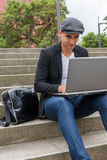 Student working on his laptop with an Irish cap. Young man with Irish beret sitting on a wall next to an urban stairs and a shoulder bag near Royalty Free Stock Photos