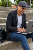 Student working on his laptop with an Irish cap. Young man with Irish beret sitting on a wall next to an urban stairs and a shoulder bag near Stock Photo