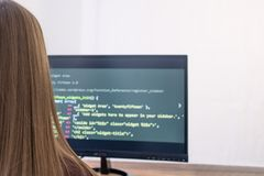 A student working at home using the computer, watching the screen. Close-up rear view over the shoulder. Program code Royalty Free Stock Photography