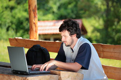 Student working on a laptop. College student working on a laptop in the park Stock Images