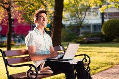 Student working on laptop sitting on a bench in the park. Student working on a laptop using books and notes sitting on a bench in a park. Young boy wearing a Royalty Free Stock Image