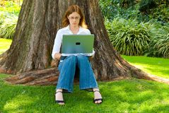 Student working outdoors. Female student with laptop working under large tree in park Stock Images