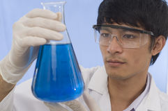 Student working in research. Scientist pouring chemicals in a laboratory Stock Image