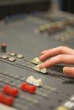 Student working on sound desk adjusting levels Stock Photos