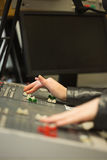 Student working on sound desk adjusting levels in the studio Royalty Free Stock Image