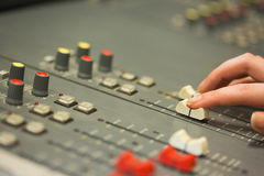 Student working on sound mixer adjusting levels. In college Stock Photography