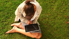Student working with tablet pc sitting on grass