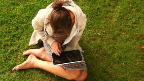 Student working with tablet pc sitting on lawn Stock Photo