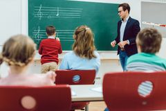 Student working with teacher at the board in front of class. Writing musical notes stock photo
