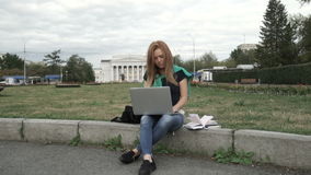 A student works on a computer. On the grass near the University stock video footage