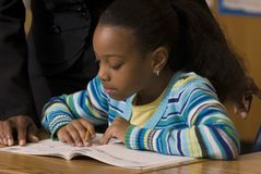 Student works in workbook during school. Student works in her workbook as teacher look over her shoulder royalty free stock images