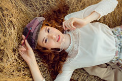 Student or writer on the nature concept. Woman writer concept. Student thinking and looking at camera lying on yellow grass outdoors. Joyful happy girl student Royalty Free Stock Photo