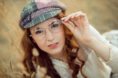 Student or writer on the nature concept. Woman writer concept. Student thinking and looking at camera lying on yellow grass outdoors. Joyful happy girl student Royalty Free Stock Photos