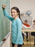 Student writing on blackboard Stock Photo