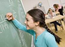 Student writing on blackboard Stock Image