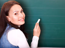 Student writing on blackboard. Stock Photo
