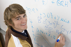 Student Writing On Board. Portrait of happy student writing on board with blue marker Royalty Free Stock Images