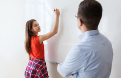 Student writing on board and teacher at school Stock Photography