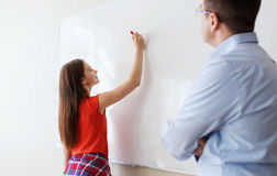 Student writing on board and teacher at school. Education, school, learning and people concept - student girl writing something on blank white board and teacher Royalty Free Stock Photos