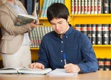 Student Writing In Book bij Universiteitsbibliotheek royalty-vrije stock foto's