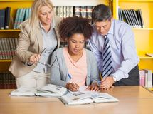 Student Writing In Book While Teachers Assisting. Beautiful university student writing in book while teachers assisting her at library Royalty Free Stock Photos